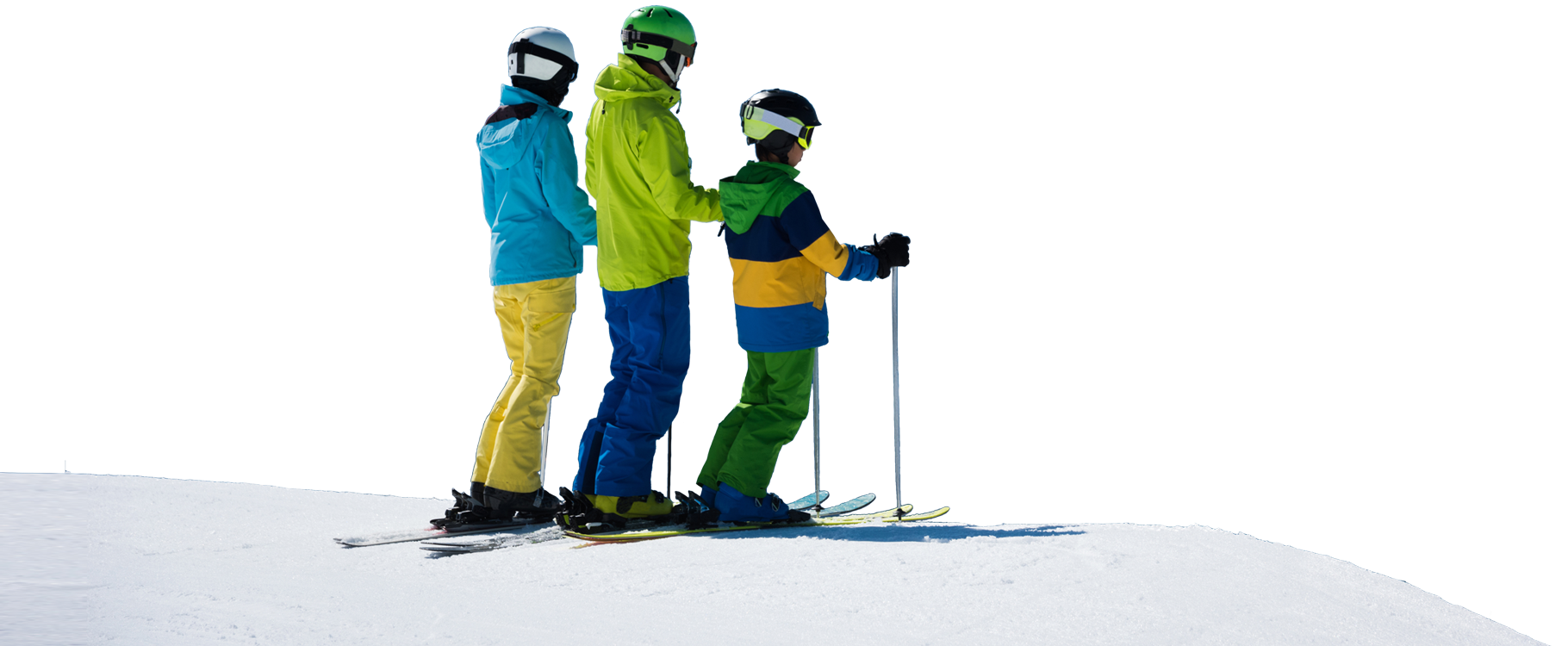Three kids dressed in brightly colored ski wear stand on their skis while taking in the view